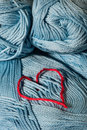 Knitted red heart on blue balls of yarn Stock Photography