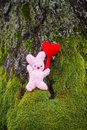 Knitted toy bunny with decorative heart on green moss in forest.