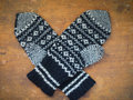 Knitted winter gloves on a wooden table Stock Image
