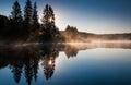 太阳通过杉树和雾发光在日出,在云杉的knob湖,西 吉尼亚 库存图片