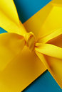 Knot in yellow gift ribbon Stock Photos