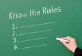 Know the rules compliance chalkboard female hand holding chalk and writing on board words with a numbered checklist Stock Photo