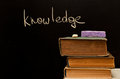 Knowledge written on chalkboard with old books Stock Photography