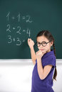 She knows the answer confident little schoolgirl thinking about right near blackboard Royalty Free Stock Photography