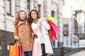 She knows where are the best prices two beautiful young women s standing with shopping bags in their hands while one of them Stock Photos