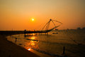Kochi chinese fishnets and the boat with fishermen on sunset Royalty Free Stock Photo