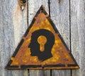 Kopf mit einer schlüsselloch ikone auf rusty warning sign Stockbild