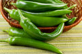 Korean green peppers falling out of basket closeup horizontal photo fresh with textured table cloth underneath Stock Image