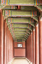 Korean palace corridor a long in the gyeongbokgung complex is flanked by red wood columns on both sides and decorated green roof Royalty Free Stock Photo
