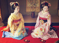 Kosen and Mamechiho Geishas pose in japanese room Royalty Free Stock Photography
