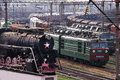 Kozyatyn,  Ukraine - April 10, 2010: Old historic steam train and new freight trains. Royalty Free Stock Photo