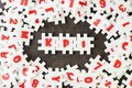 stock image of  KPI, Key Point Indicator concept, white puzzle jigsaw alphabet combine word KPI at the center on dark black cement floor, business