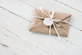 Kraft envelope with teg with heart and ribbon on white wooden tabletop