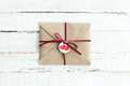 Kraft envelope with teg with two hearts and ribbon on white wooden tabletop