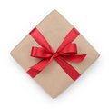 Kraft paper gift box with ribbon bow from above white background Stock Photos
