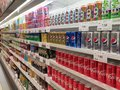 Soft drinks in cans are displayed on a shelf for sale in a large supermarket. Royalty Free Stock Photo