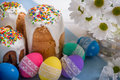 Kulich, traditional Russian Ukrainian Easter cake with icing and colored eggs with lace ribbon on white wooden background Royalty Free Stock Photo
