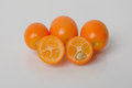 Kumquats fresh grouped together with cut in half the seed is the same size as a tangerine s showing size perspective Stock Images