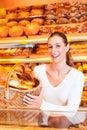Kvinnligbagare som säljer bröd i henne bageri Arkivfoton