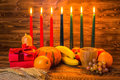 Kwanzaa holiday concept with traditional lit candles, gift box, Royalty Free Stock Photo