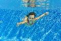 L enfant sous marin actif heureux nage dans la piscine belle natation saine de fille et amusement de avoir des vacances d été de Photo stock