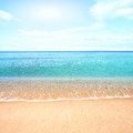 Sandy beach with calm water against blue skies. Royalty Free Stock Photo