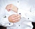L uomo indossa i gemelli su una manica della camicia uno sposo che mette sui gemelli come si veste nell usura convenzionale Immagini Stock
