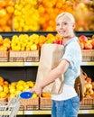 La fille avec le chariot remet le paquet avec les légumes frais Photos stock