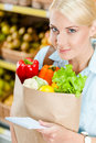 La fille remet le paquet avec la liste de lecture de légumes frais de produits Photo stock