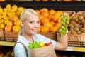 La fille remet le paquet avec les légumes frais choisissant le raisin Photographie stock