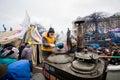 La giovane donna versa il tè caldo da un barilotto enorme della cucina della via sul quadrato ammucchiato di maidan durante la Fotografia Stock