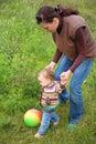 La madre y el bebé juegan con la bola en hierba Imagenes de archivo