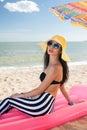 La muchacha tiene un resto en la playa Foto de archivo libre de regalías