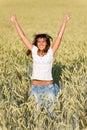 La mujer feliz salta en campo de maíz en verano Imagenes de archivo
