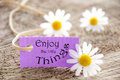 Label with enjoy the little things a purple saying and flowers in background Royalty Free Stock Photography