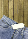 Label tag and jeans on wood background Royalty Free Stock Photo