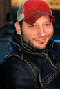 Labor worker closeup of an unshaven smiling male wearing a leather jacket and red ball cap shallow depth of field Royalty Free Stock Photos