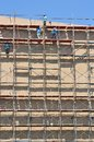 Labor working on high scaffold in construction site Royalty Free Stock Photos