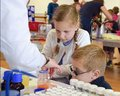 Laboratory chemists tak a day out of the lab to teach children about chemistry as part of the UK STEM, science, technology,engine