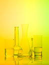Laboratory glass recipients on yellow background frontal view of different types of containers used in the filled with transparent Stock Images