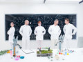 Laboratory researcher team general view of five confident people in a chemistry lab around lab tools leafs and colorful liquids Royalty Free Stock Photography