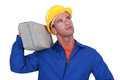 Laborer carrying heavy cinderblock Royalty Free Stock Photos