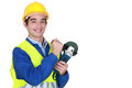 Laborer holding sander smiling an electric Stock Photo