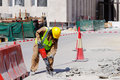 A laborer uses a jackhammer to break up a concrete pavement is well protected in safety gear as he reinforced Royalty Free Stock Photos