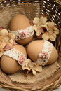 Lace decorated easter eggs with and artificial flowers in a basket Royalty Free Stock Photos