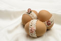 Lace decorated easter eggs with and artificial flowers on silken background Royalty Free Stock Photo