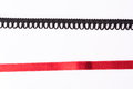 Lace trim ribbon over white. Black and red Royalty Free Stock Photo