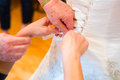 Lacing up wedding dress bride wearing white getting laced by a friend and mother Royalty Free Stock Images