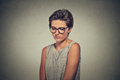 Lack of confidence shy young woman in glasses feels awkward on grey wall background human emotion body language life perception Royalty Free Stock Photos