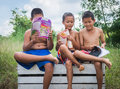 Lack of education poverty countryside boys sitting together reading books and enjoy concept Stock Photography